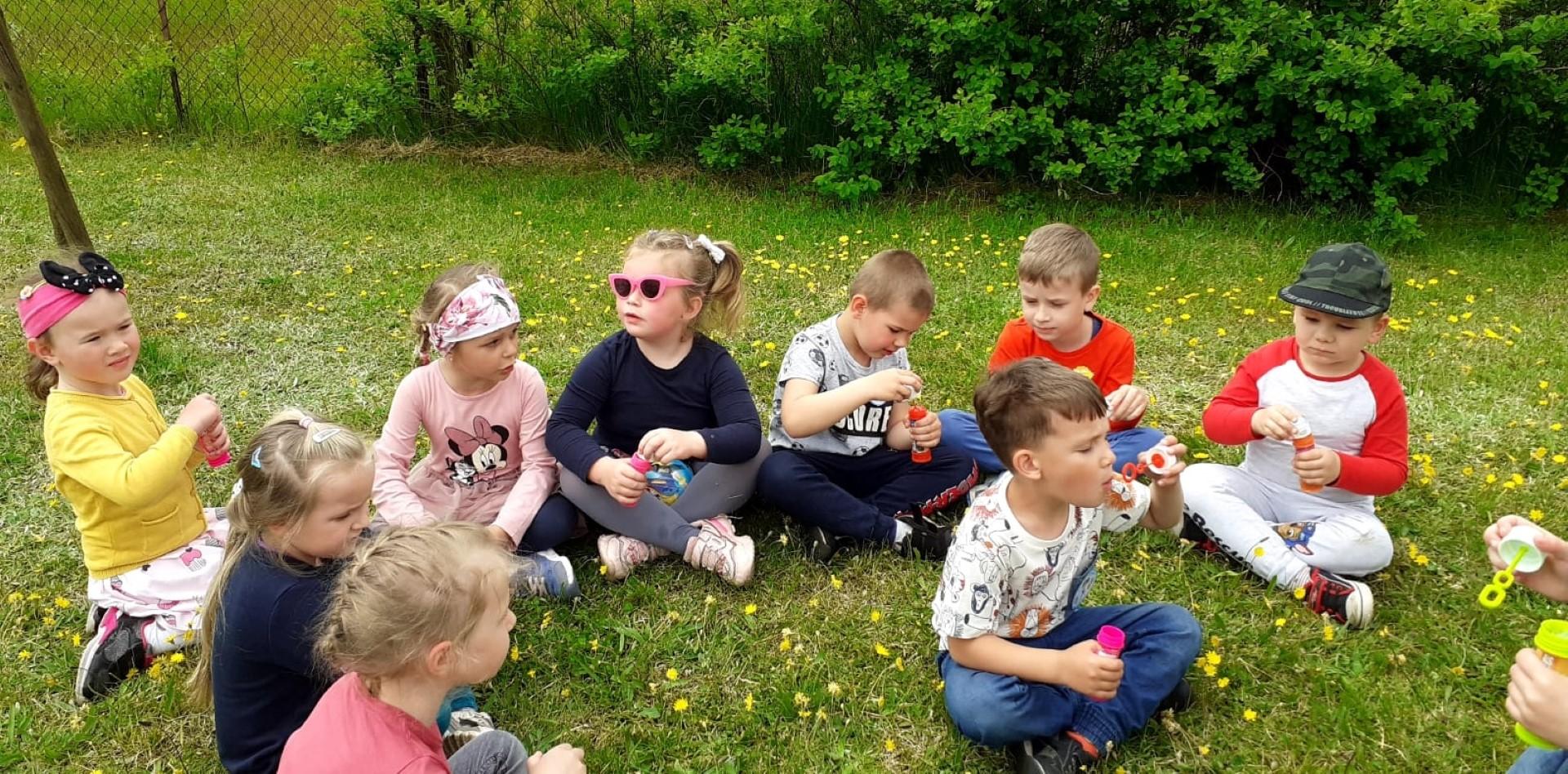 Przedszkolaki siedzą na trawie i dmuchają bańki mydlane.