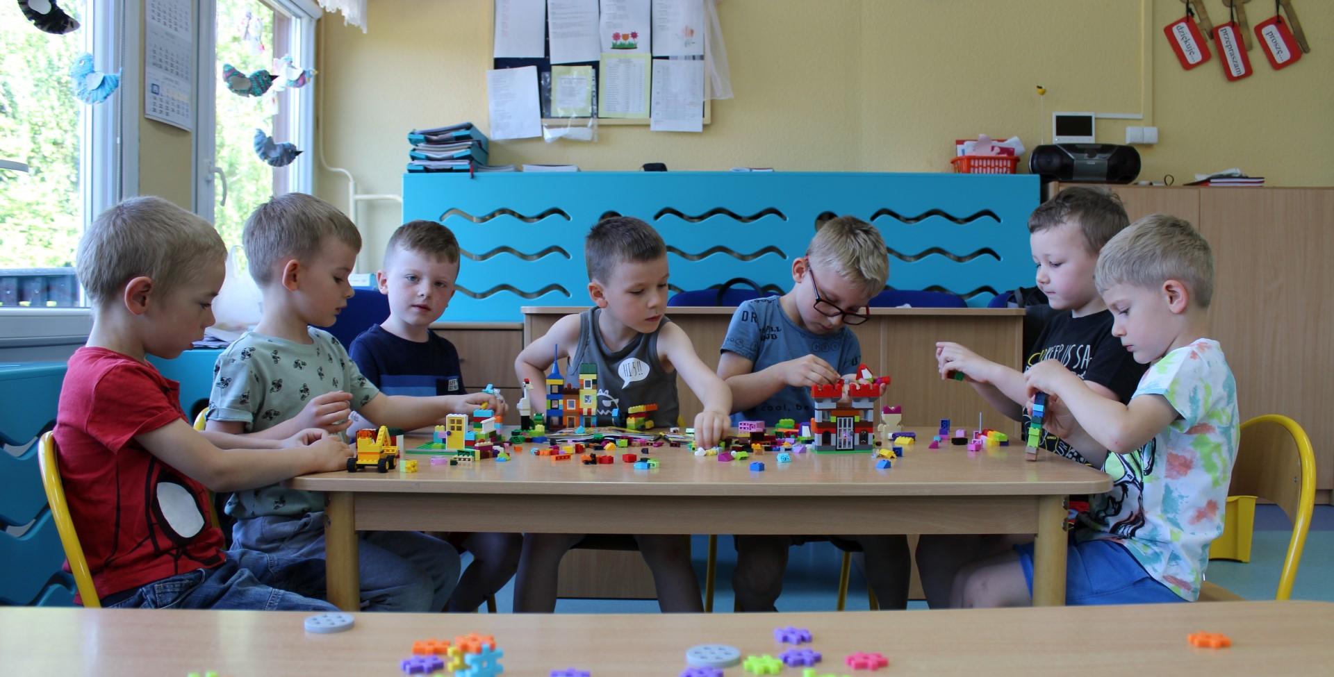 Chłopcy budują różne budowle z klocków lego.