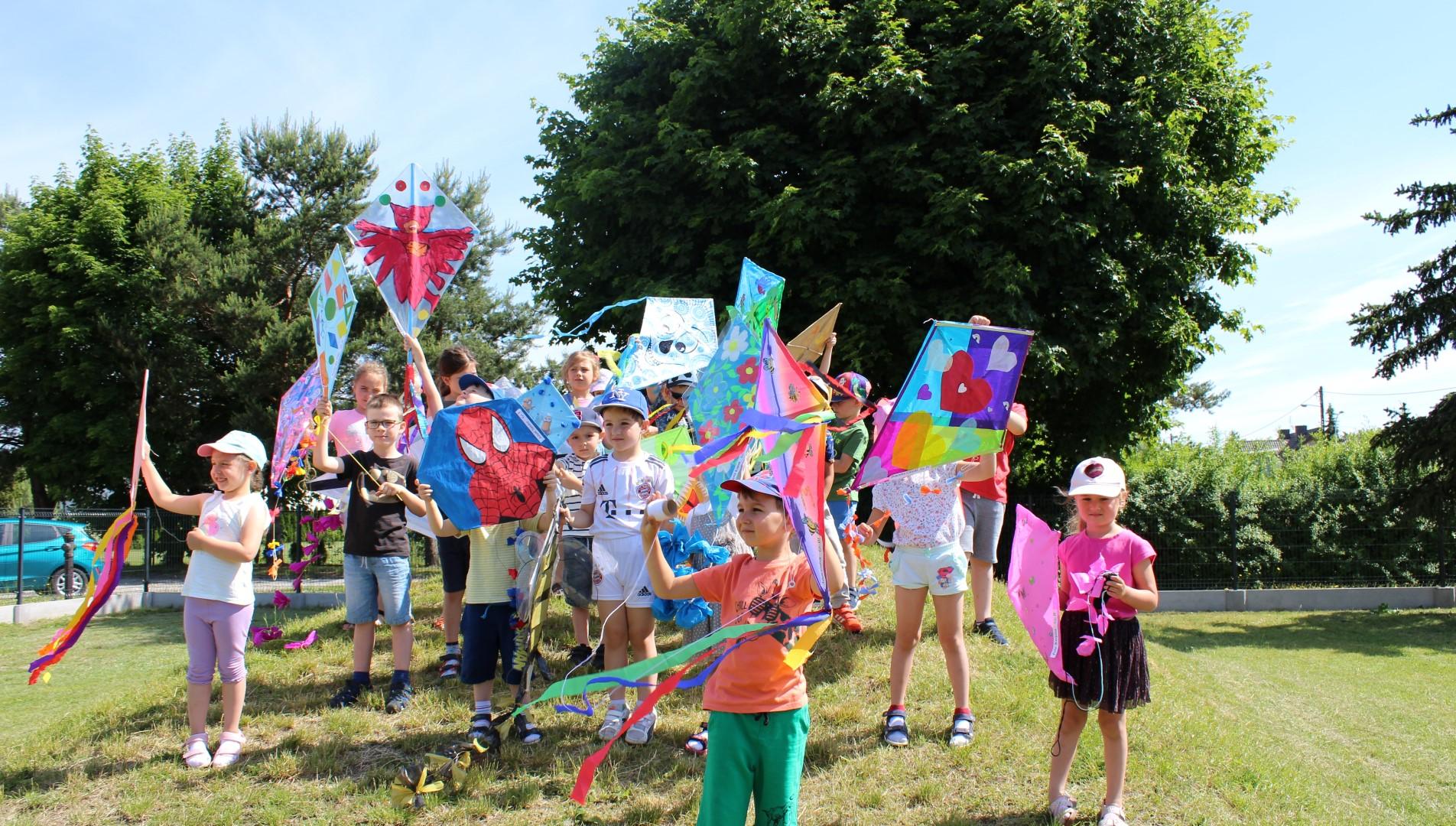 Dzieci z latawcami stoją na podwórku przedszkolnym.